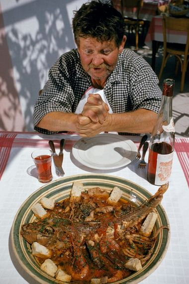 In the port town of Positano, a man prepares to dine on zuppa di pesce – ...