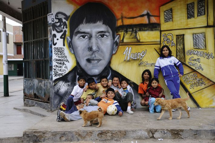 Locals strike a pose in front of a mural painting, Callao
