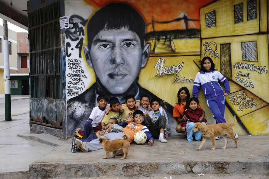 Locals strike a pose in front of a mural painting, Callao.