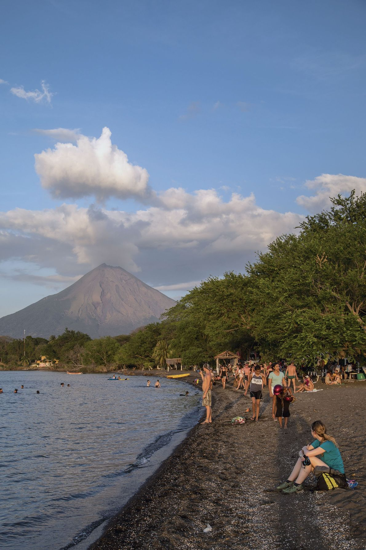 Tourists watch sunset on the dark shores of Ometepe Island