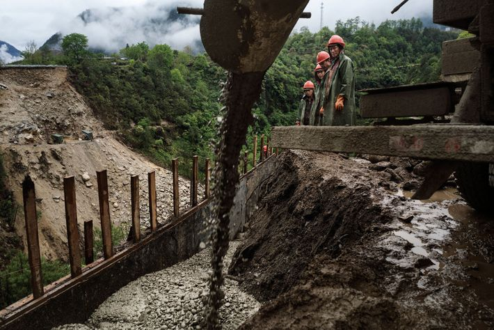 Construction workers from central Yunnan build a bridge in the village of Zhong Ding along the ...