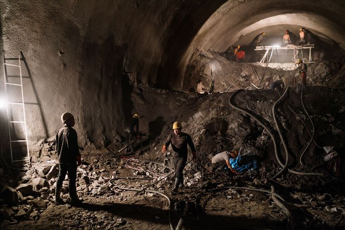 Construction workers labour inside the Huipo Tunnel construction project that will allow a highway to run ...