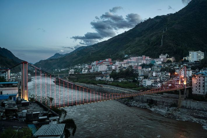 A suspension bridge over the Nu River is illuminated in Fugong, one of the largest towns ...