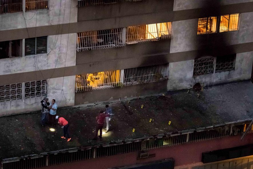 Security forces examine evidence of a drone-borne explosion in Caracas, Venezuela in August 2018, when President ...