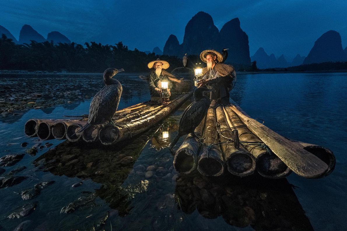 Picture of two fishermen and their trained cormorants on rafts on a river in China