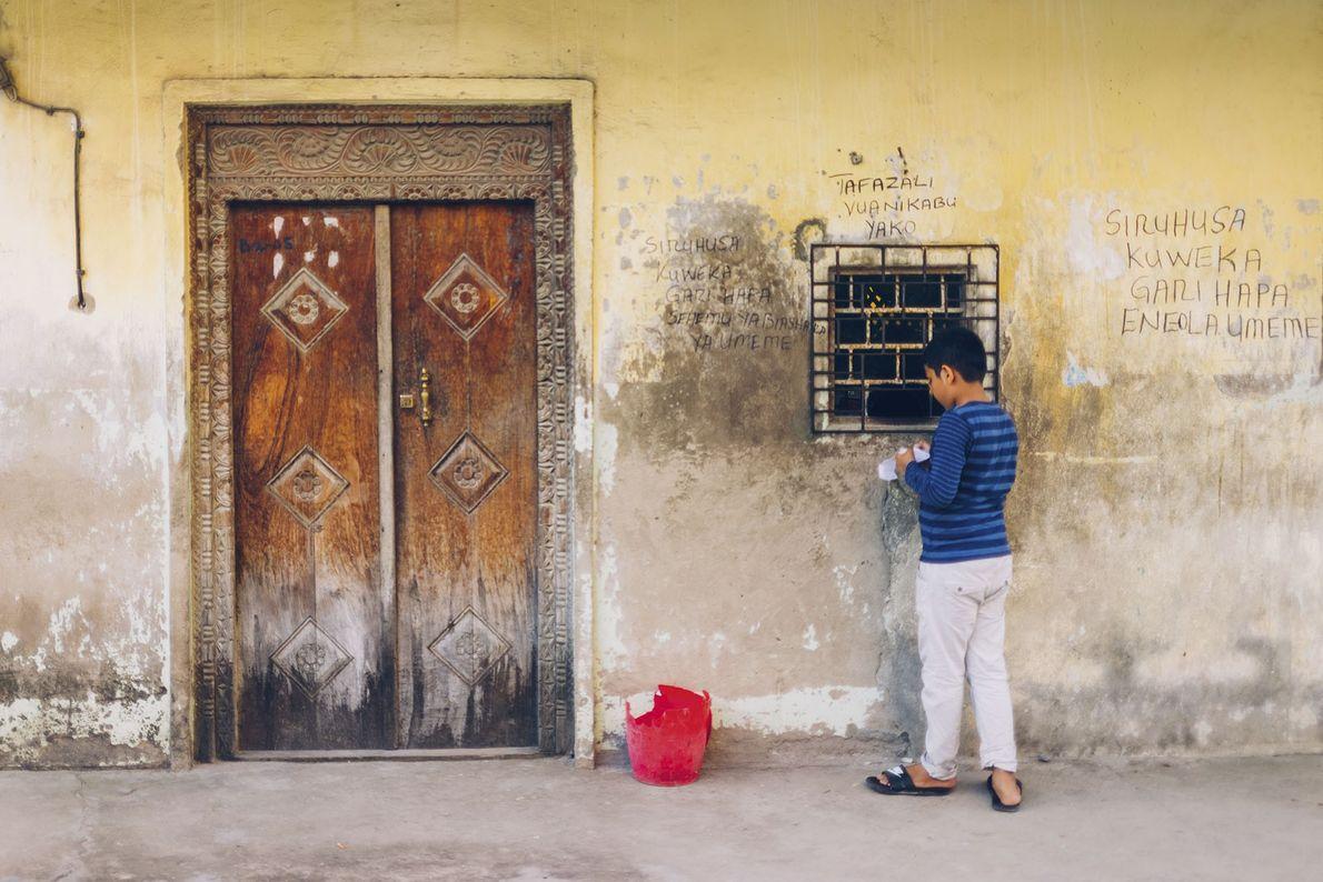 A kid stands next to a door.