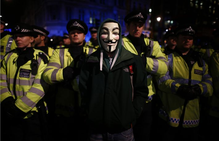 A protester wearing a Guy Fawkes mask stands infront of a line of riot police officers ...