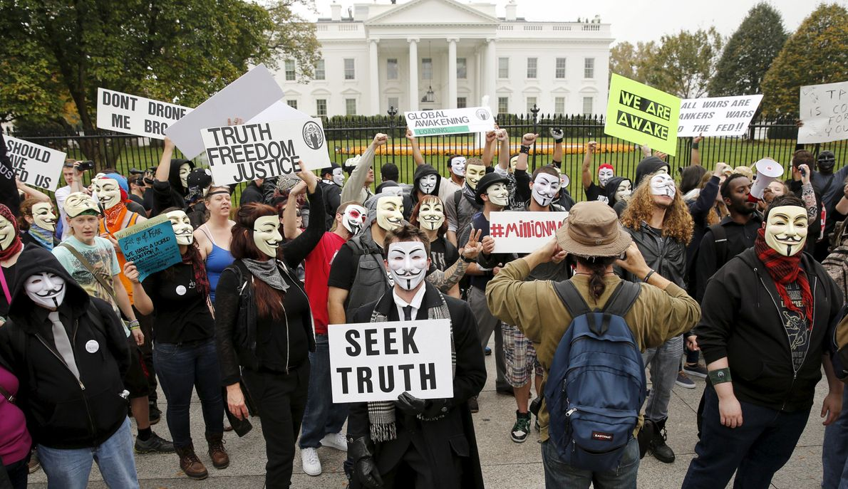 Protesters aligning themselves with the hacktivist group Anonymous, with their signature Guy Fawkes masks, gather in ...