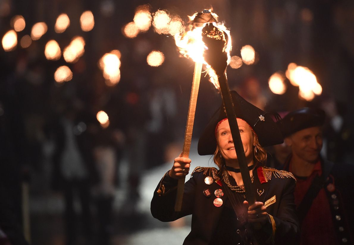 Participants in costume hold burning torches as they take part in one of a series of ...