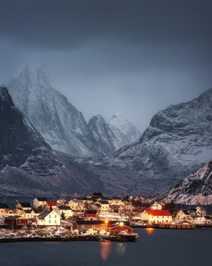 The lights of Reine, on Moskenesøya, in the Lofoten archipelago, with its backdrop of dramatic mountains. ...