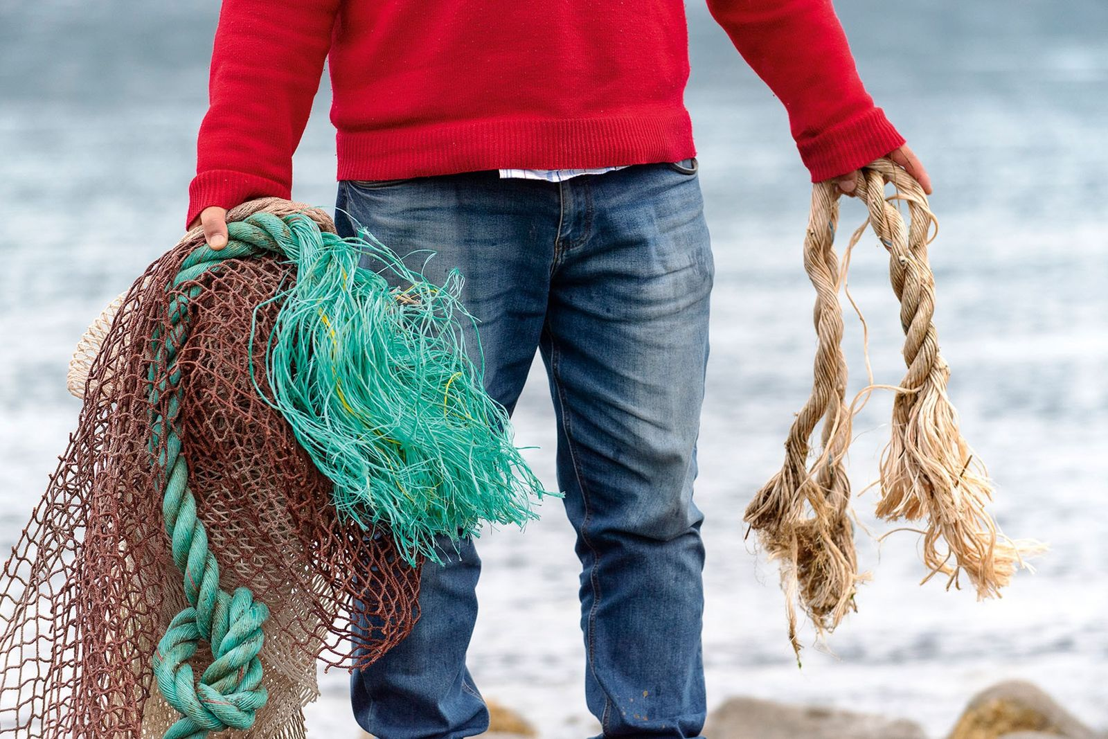 Man collecting netting from beach