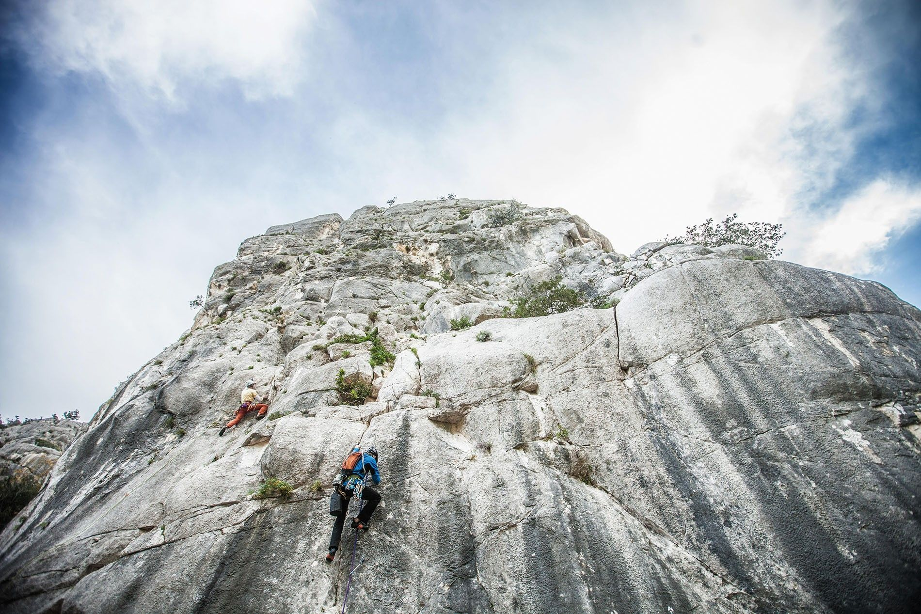 Rock climbers on the vertical cliffs at Ogliastra