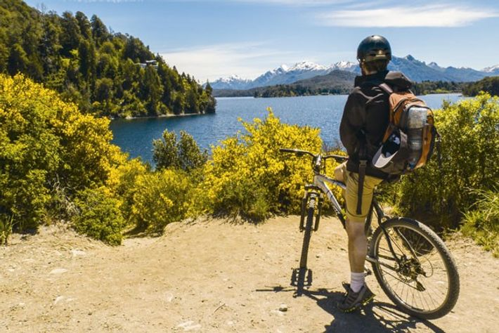 A mountain biker looking out over a lake in Bariloche.