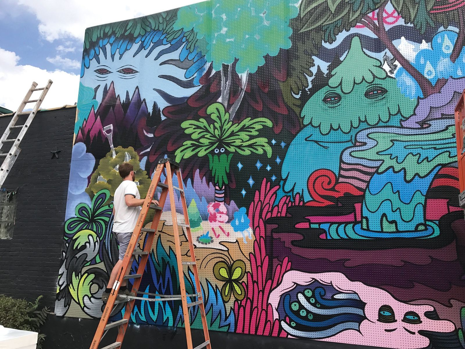 Artist Rather Severe working on a mural