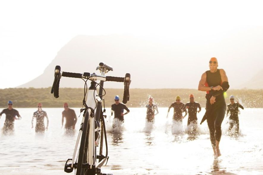 Triathletes running to bicycles on the beach
