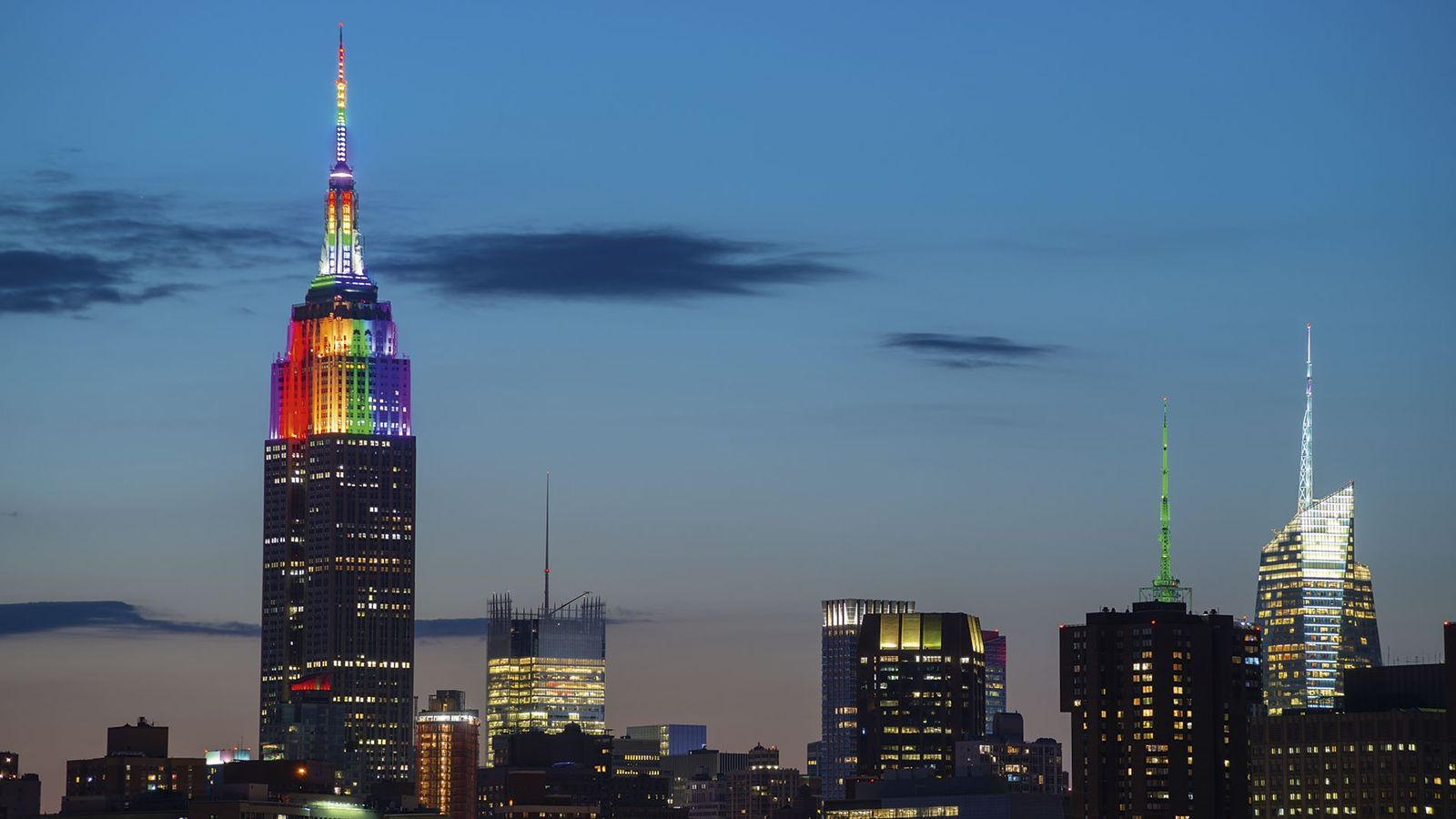 A skyline of Manhattan with the Empire State Building displaying Pride colours