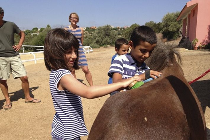 The kids groom their ponies at Officina Equestre.