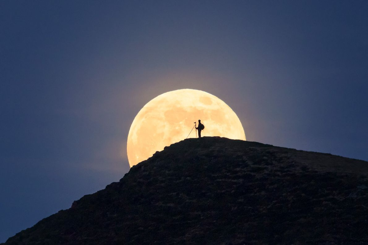 "Alyn Wallace: ""A photographer on Cribyn in the Brecon Beacons Dark Sky Reserve eclipsing the rising ..."