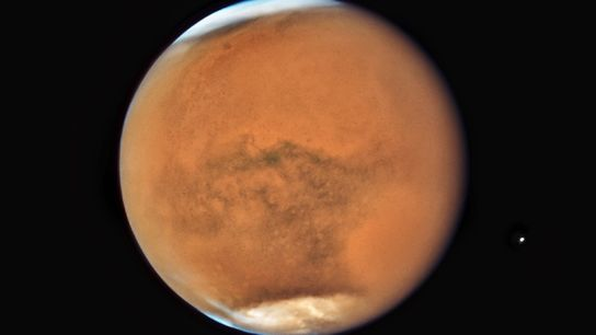 This image of Mars, captured by the NASA/ESA Hubble Space Telescope, reveals the red planet smothered ...