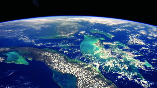 The shallow waters and reefs surrounding Cuba (foreground), Florida (middle), and the Bahamas (right), as seen ...