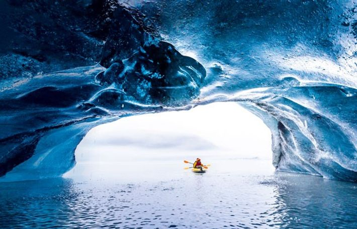 Kayaking out of a blue ice cave near the port of Valdez, Prince William Sound.