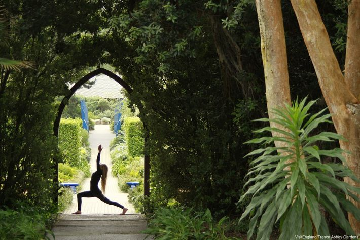Woman striking a yoga pose under an arch at The Abbey Gardens in Tresco on the ...