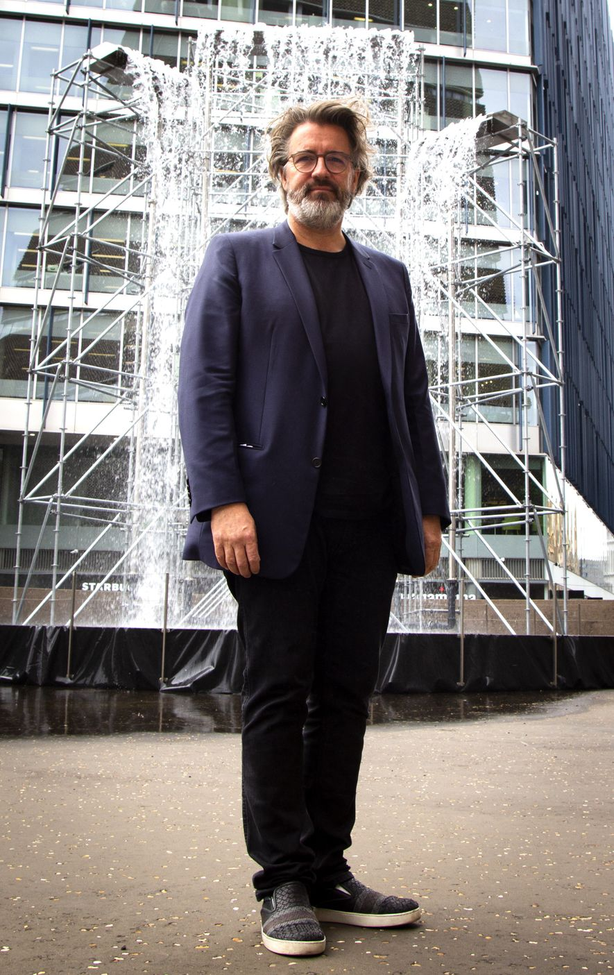 Olafur Eliasson in front of the waterfall installation, Tate Modern.