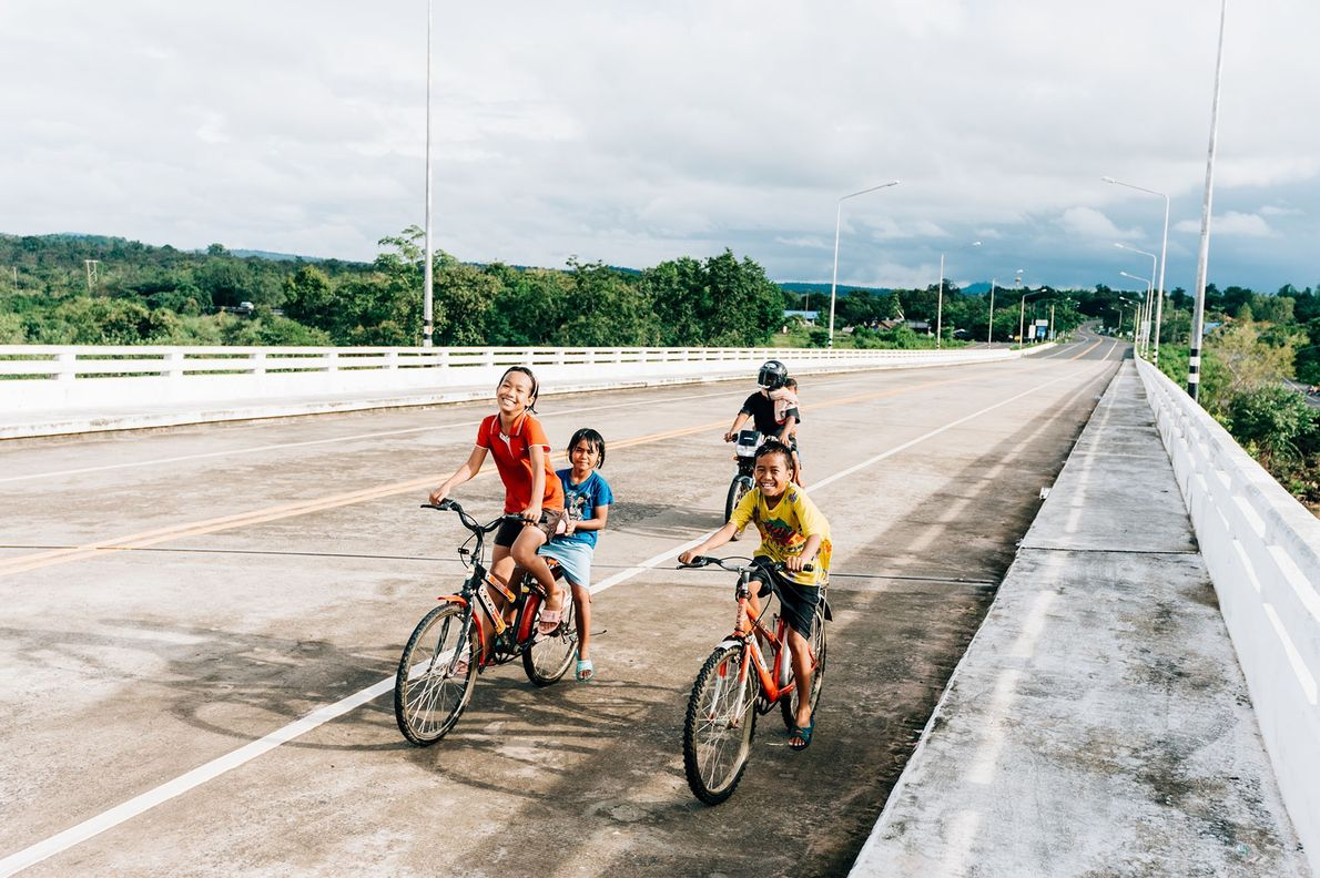 Kids cycling on a bridge that crosses the Mun river close to Khong Jiam