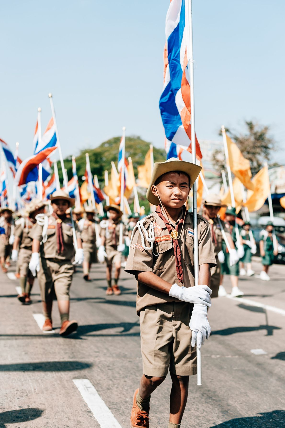 Scouts carrying the Thai flag join a two-kilometre long procession for the King's Birthday Parade in ...