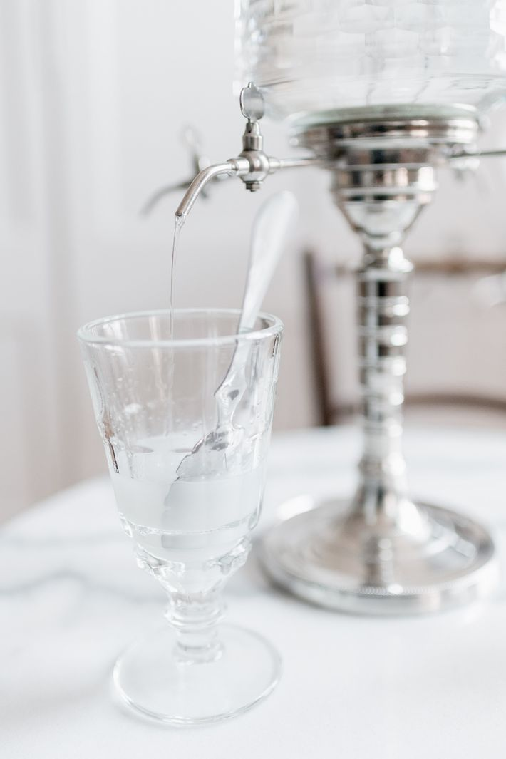 Ice-cold water pours from an absinthe fountain into a glass of the spirit, turning the liquid ...