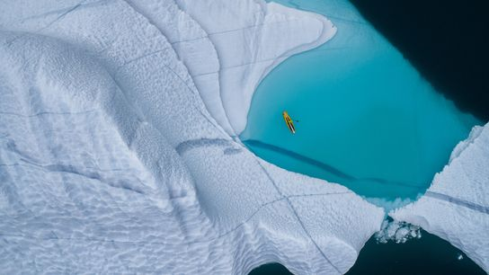 A stand-up paddleboarder cuts through the frigid waters of theGreenland Sea.