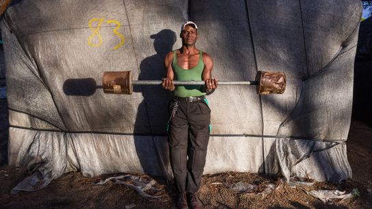 Issa Diakite, 50, built both his barbell and his home, one of dozens of chabolas clustered ...