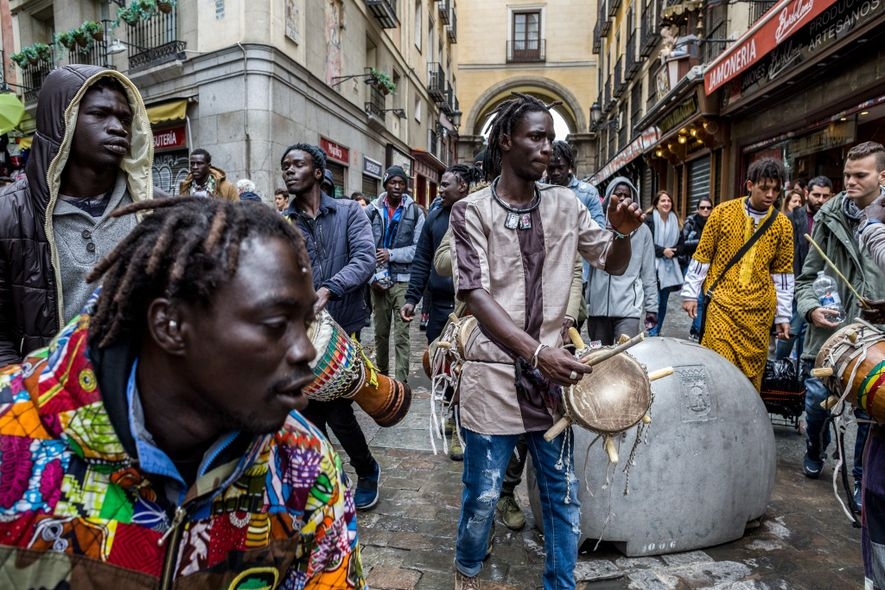 At an entrance to Madrid's historic Plaza Mayor, Senegalese migrants take a break from their labors ...