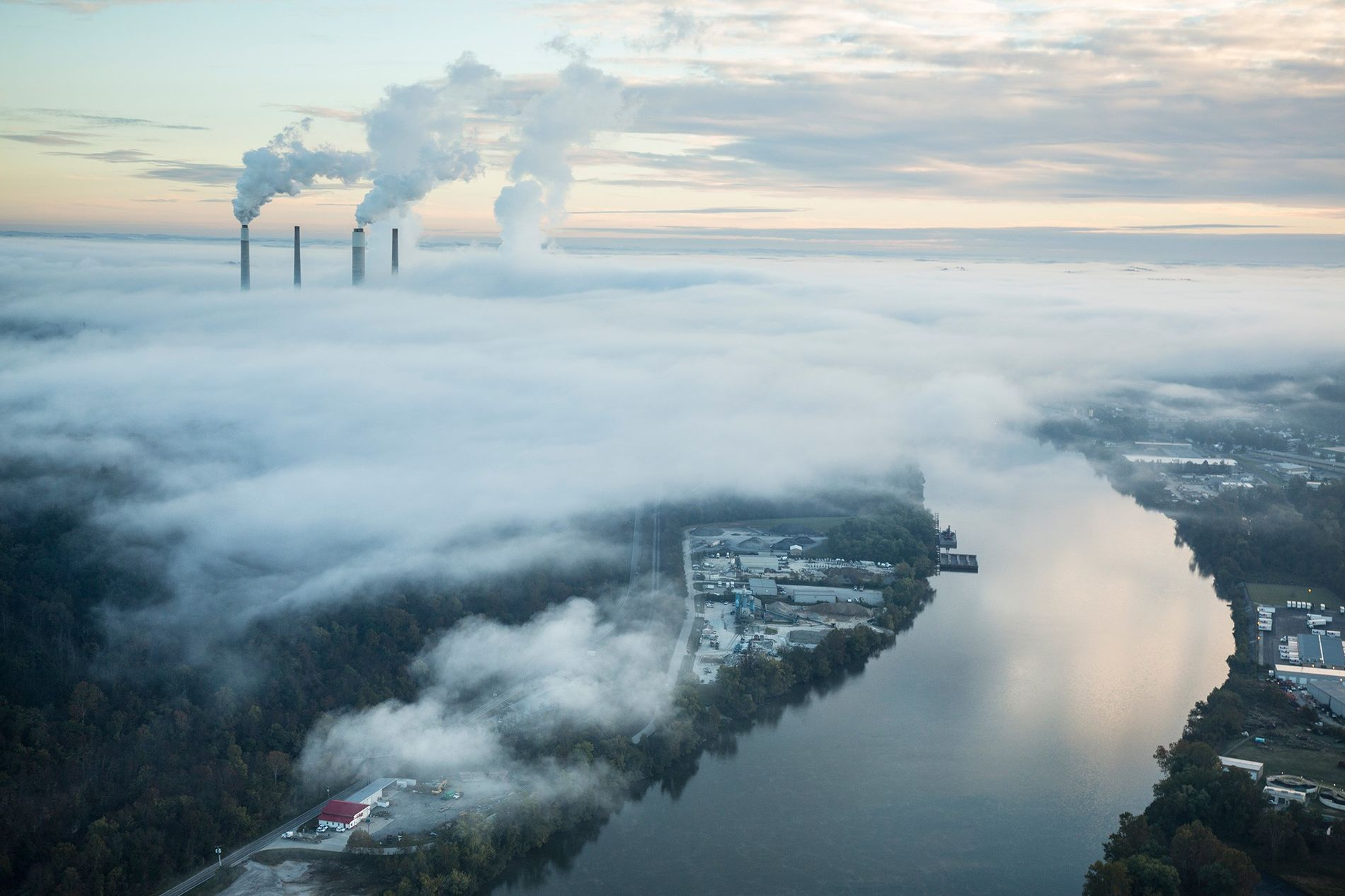 Steam and smoke rise from the cooling towers and chimneys of a power plant. Artificial intelligence ...