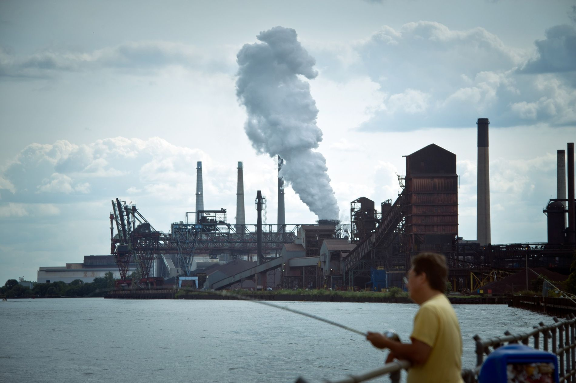 A man fishes near a DTE coal plant in Detroit.