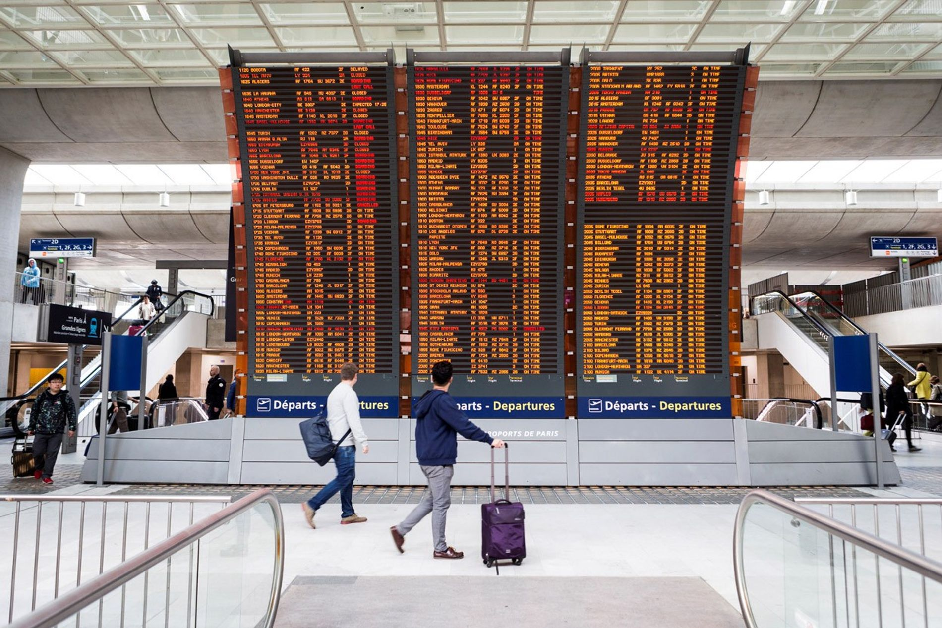 Passengers check the departures board at Charles de Gaulle Airport in Paris, France.  ...
