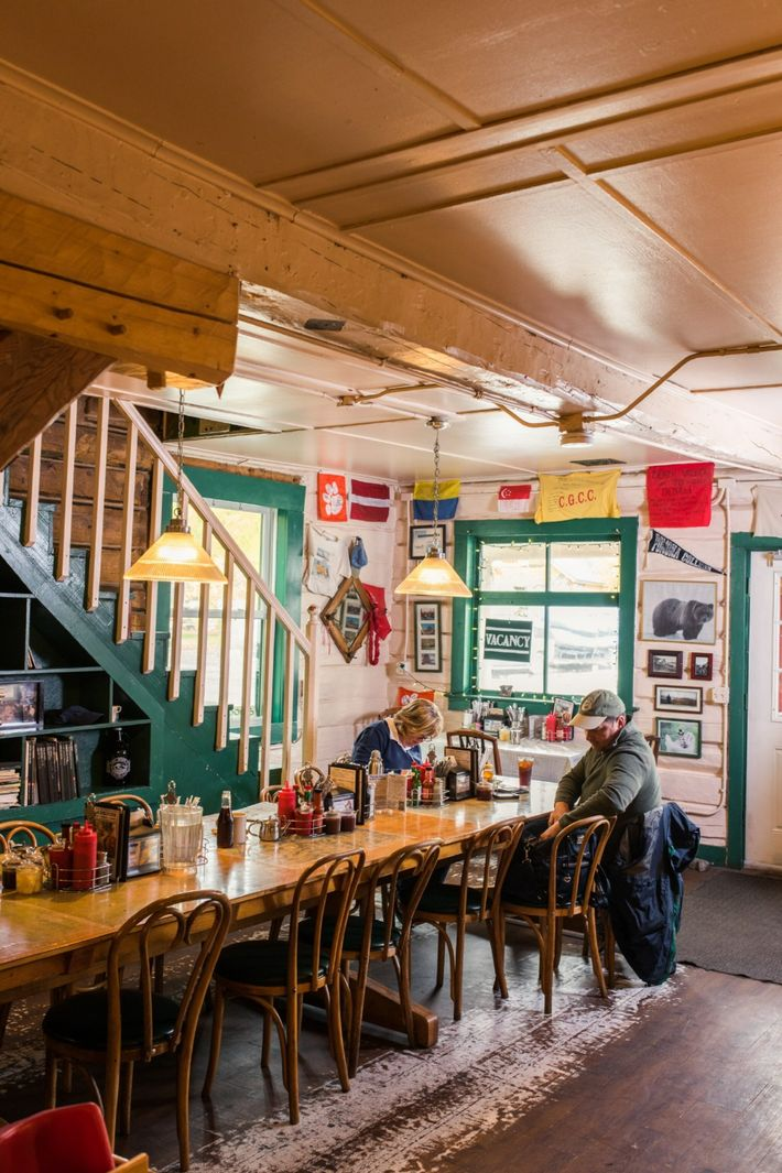 Guests dining at The Talkeetna Roadhouse. Stairs behind them lead up to the guest rooms.