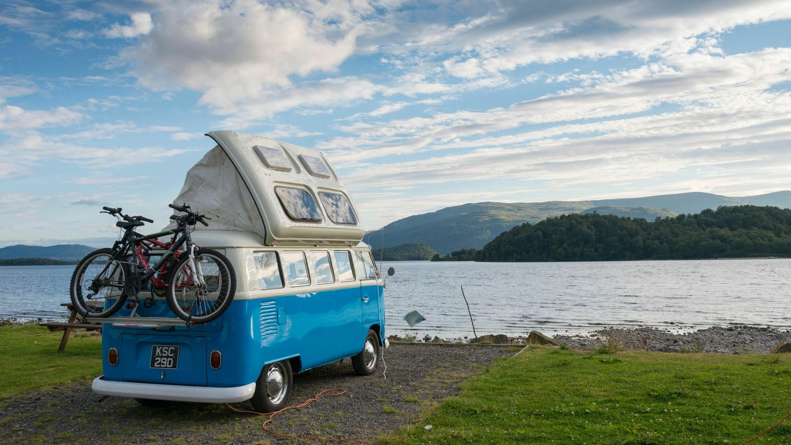 A blue VW campervan parked on the shore of Loch Lomond, Scotland.