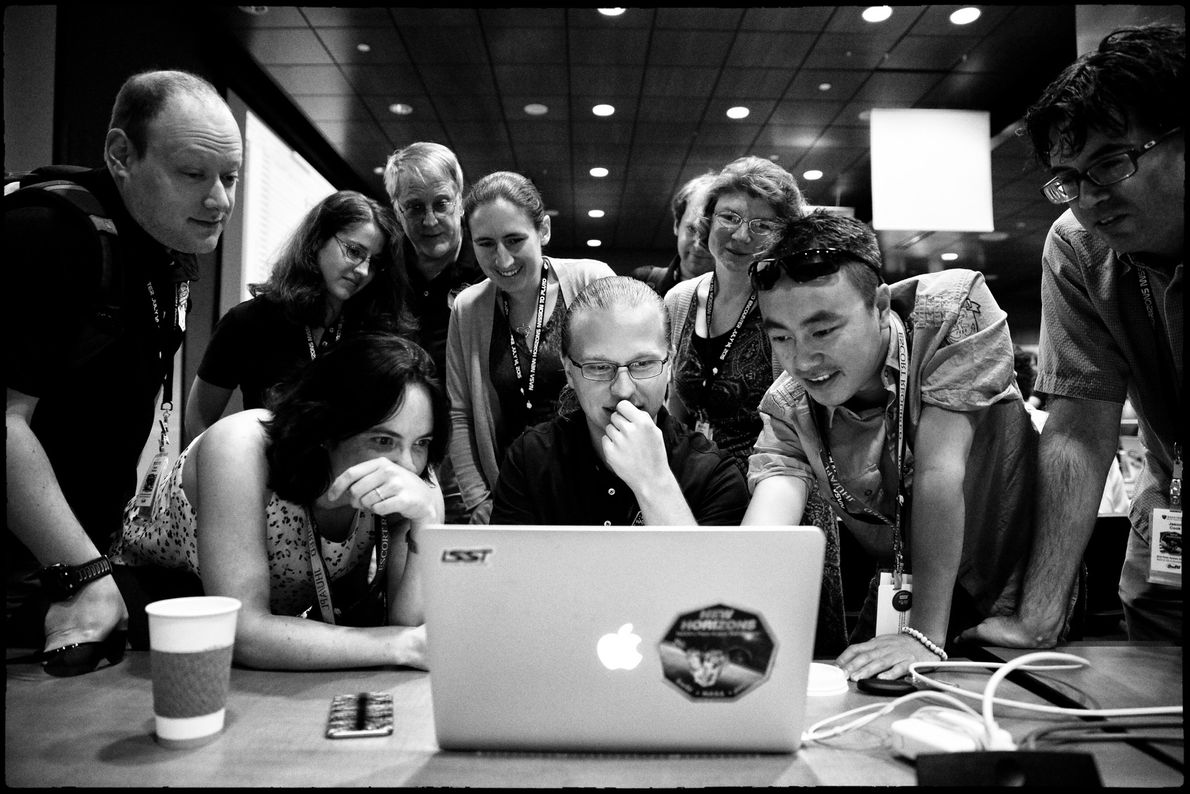 Alex Parker (centre) and other members of the New Horizons team joyously react to the latest ...