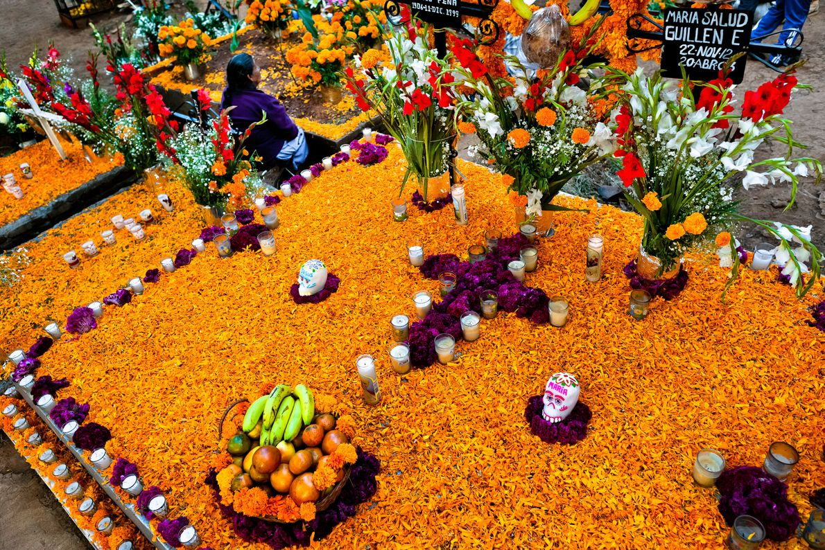 A Mexican woman sits at at a gravesite covered in marigolds and other flowers during a ...