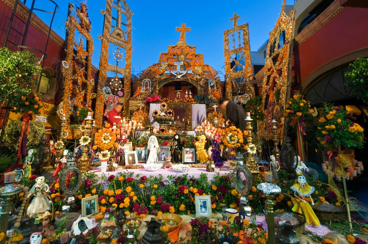 Marigolds and family photos decorate a Day of the Dead altar in San Miguel de Allende, ...