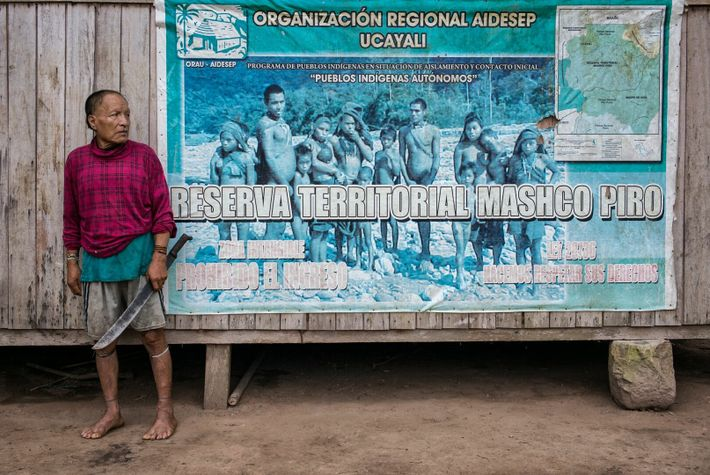 Shuri stands in front of a sign marking the control post for the Mashco Piro Indigenous ...