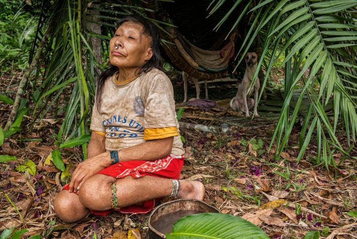 Shuri's mother-in-law, Maria, sits with her two pet dogs at the shelter she built behind the ...