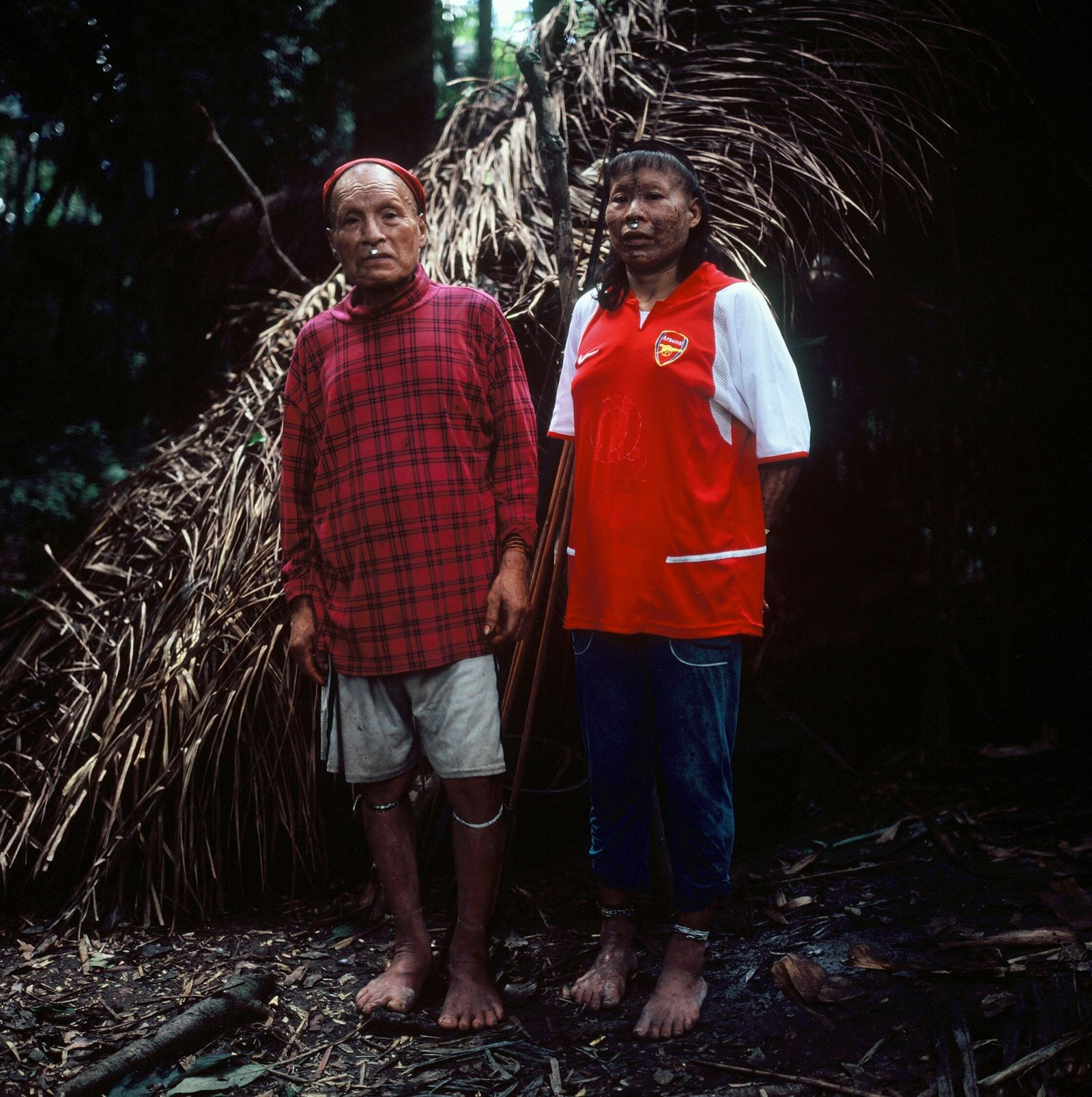 Shuri and wife Janet stand in front of their palm-thatched shelter, or maloca, in May 2017. ...