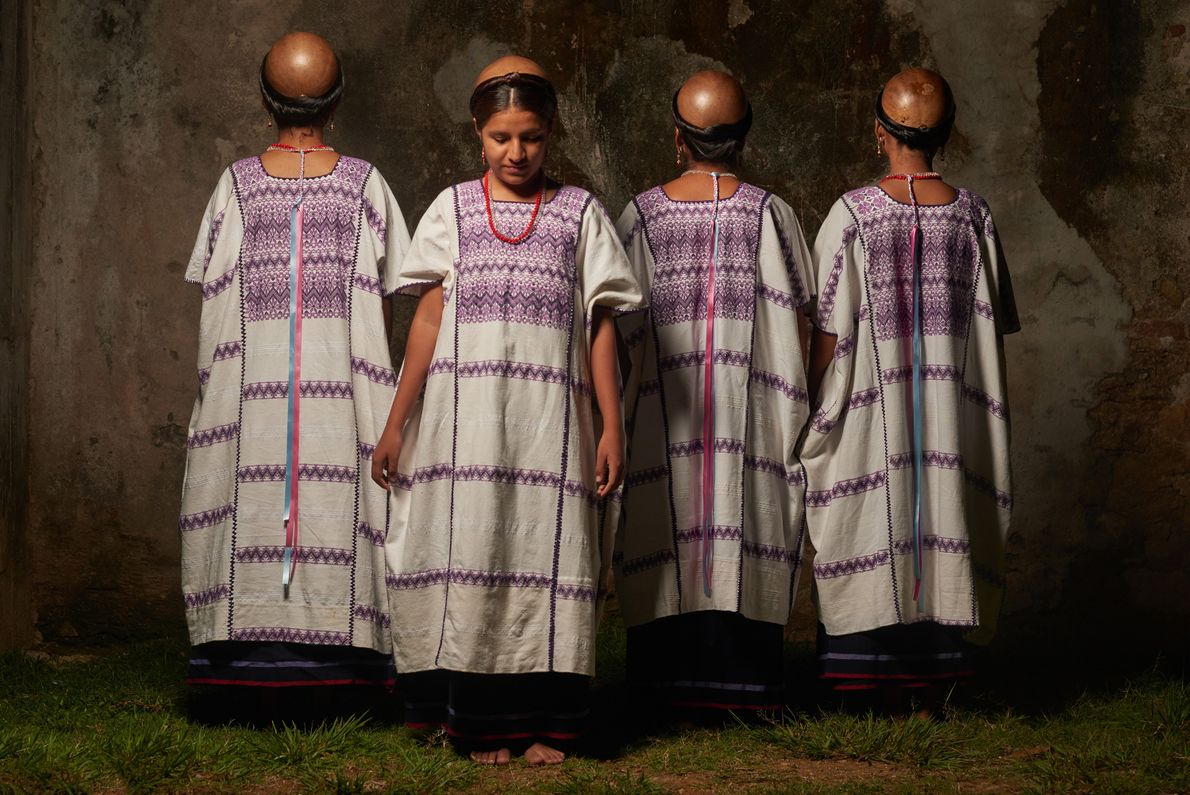 Amuzgos women wear traditional huipil dresses and gourds on their heads to cover from sun and ...