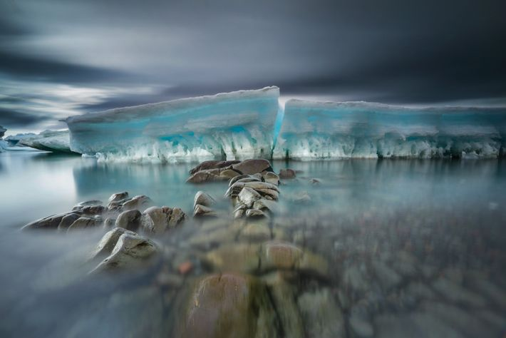 Sea-worn stones form a path to beached and broken sea ice. Ice is central to life ...