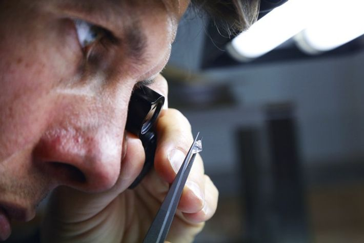 Worker examining a diamond with a magnifying glass in the Diamond District