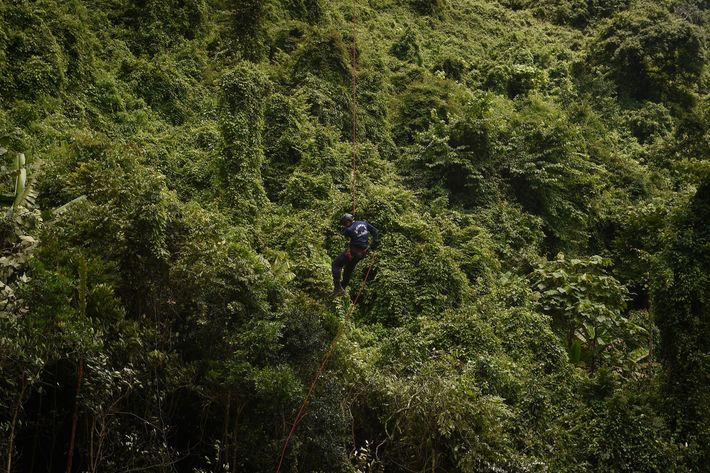 A member of the Thai Airforce repels from a helicopter into a clearing in the forest, ...