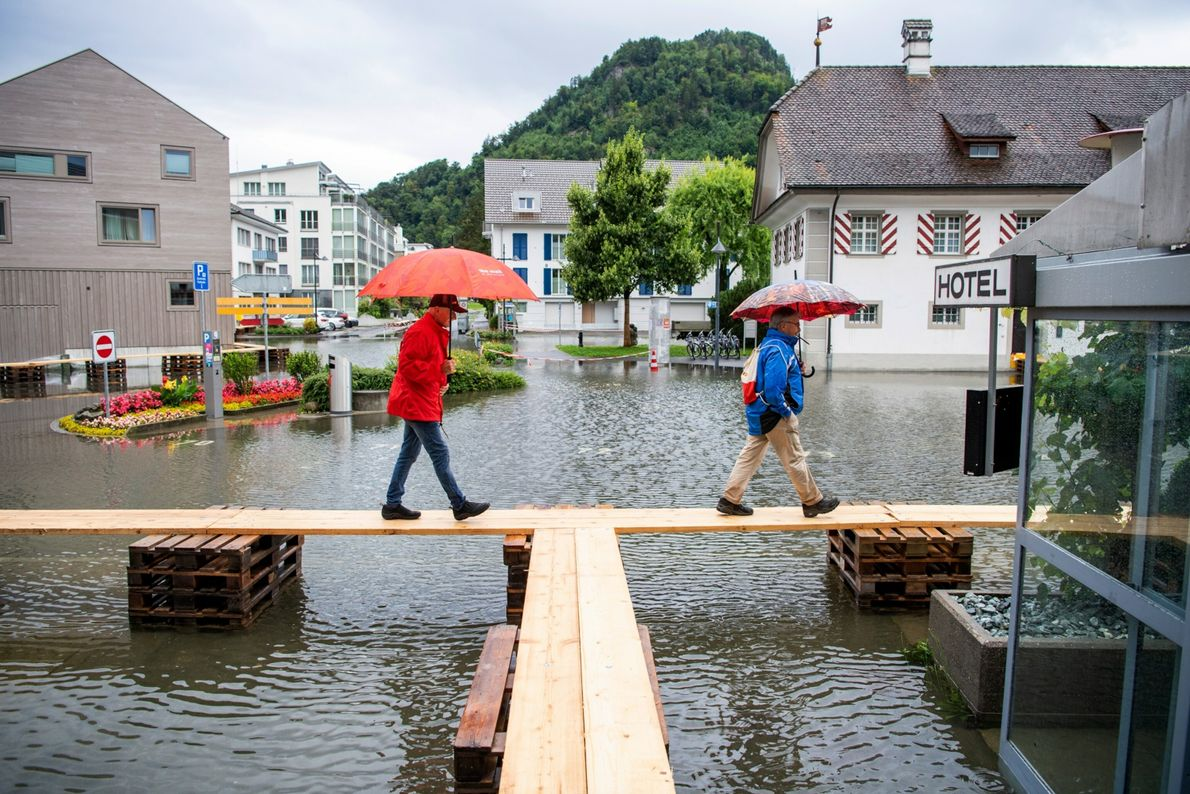 In Switzerland, people walk on footbridges in the flooded village square.