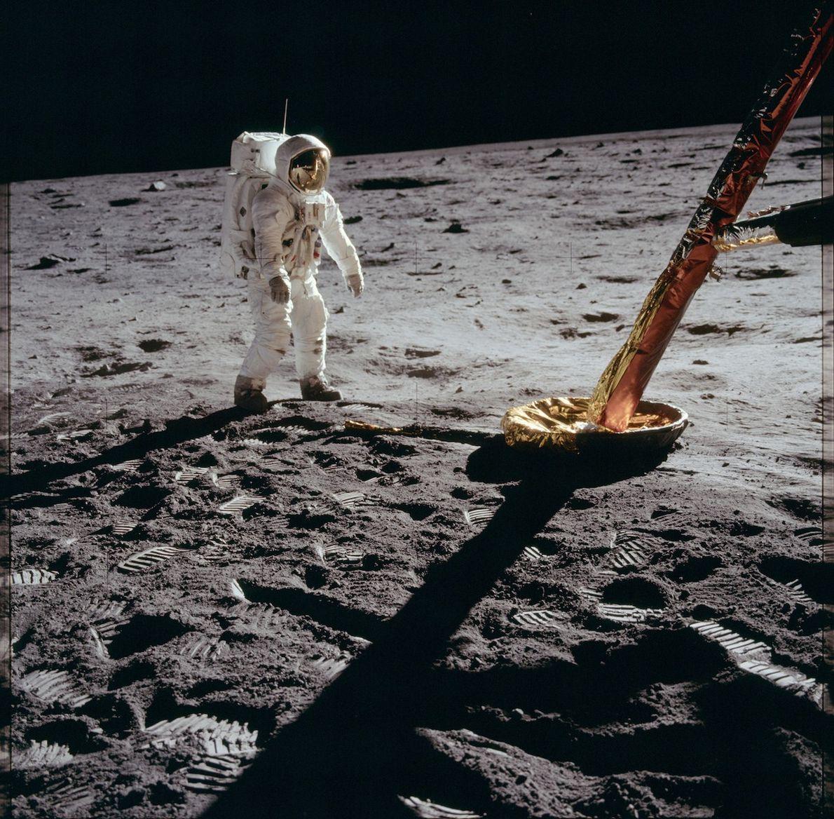 Astronaut Buzz Aldrin walks on the surface of the moon near a leg of the Eagle ...